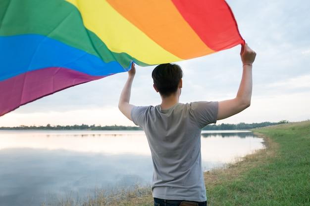 Un jeune homme blanc voit par derrière tenant un drapeau arc-en-ciel Photo Premium