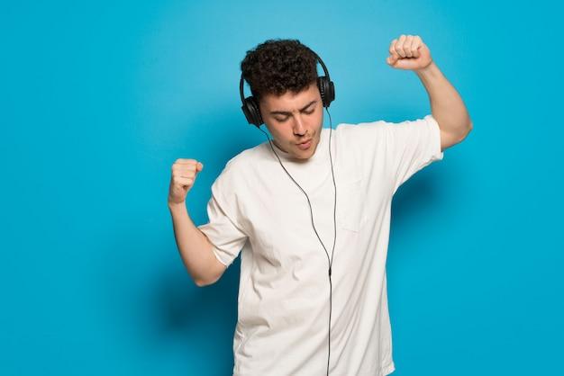 Jeune homme sur bleu, écouter de la musique avec des écouteurs et danser Photo Premium
