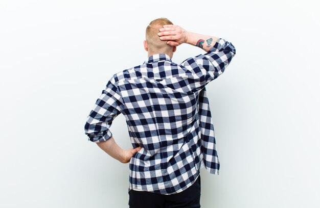 Jeune Homme Blond Avec Chemise Carrée Se Sentir Désemparé Et Confus, Pensant à Une Solution, Avec La Main Sur La Hanche Et D'autres Sur La Tête, Vue Arrière Photo Premium
