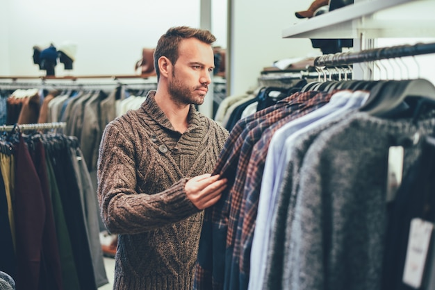 Jeune homme blond faisant des courses dans un magasin Photo Premium