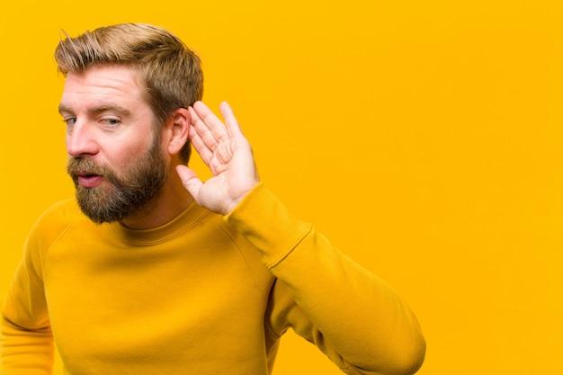 Jeune homme blond souriant regardant curieusement sur le côté en essayant d'écouter des commérages ou d'entendre un secret Photo Premium