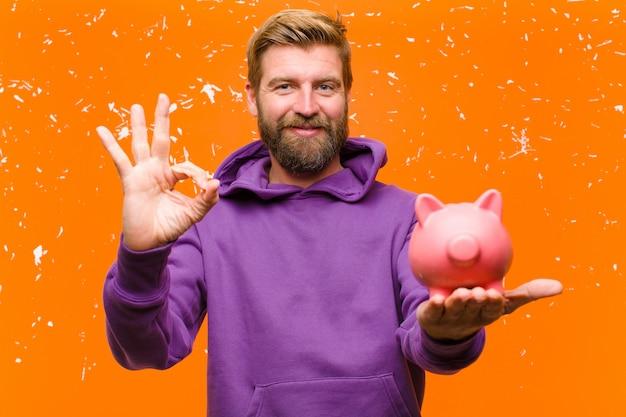 Jeune homme blond avec une tirelire portant un chandail à capuchon violet contre le mur orange endommagé Photo Premium