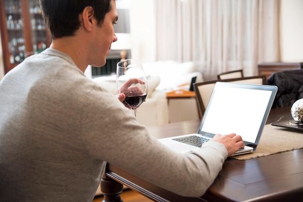 Jeune Homme Boit Du Vin Tout En Utilisant Une Tablette Numérique à La Maison Photo gratuit