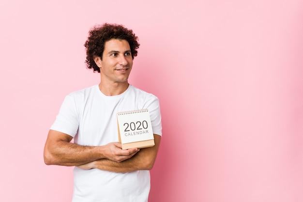 Jeune Homme Bouclé Caucasien Tenant Un Calendrier 2020 Souriant Confiant Avec Les Bras Croisés. Photo Premium