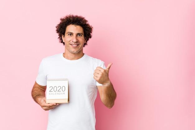 Jeune Homme Bouclé Caucasien Tenant Un Calendrier 2020 Souriant Et Levant Le Pouce Vers Le Haut Photo Premium