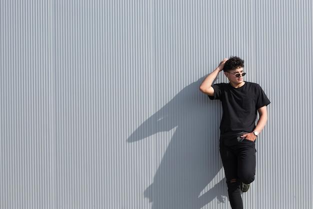 Jeune homme bouclé à lunettes de soleil et vêtements noirs se penchant sur le mur gris Photo gratuit