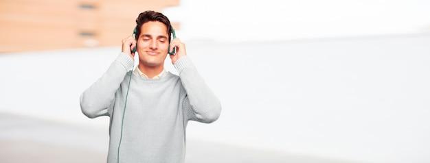Jeune homme bronzé beau écoute de la musique avec un casque Photo Premium