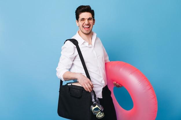 Jeune Homme Brun à Lunettes Rit. Guy En Costume Tient Un Anneau En Caoutchouc Rose Et Un Masque De Plongée. Photo gratuit