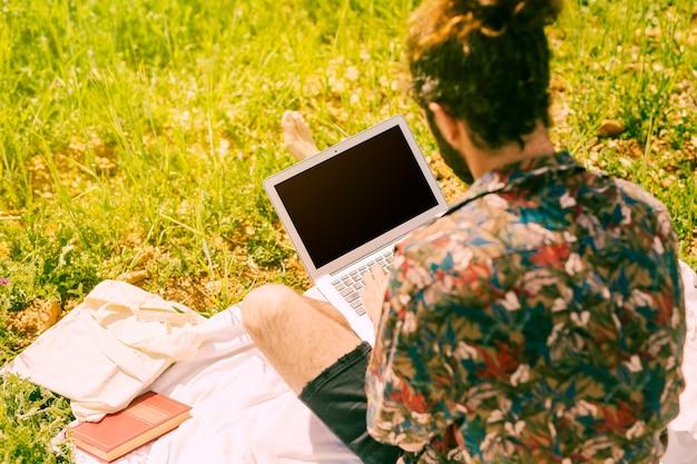 Jeune homme brune, gardant un ordinateur portable dans le pré Photo gratuit