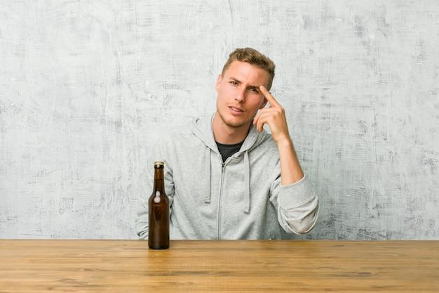 Jeune Homme Buvant Une Bière Sur Une Table Montrant Un Geste De Déception Avec L'index. Photo Premium