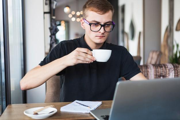Jeune homme buvant du café à la table avec un ordinateur portable Photo gratuit