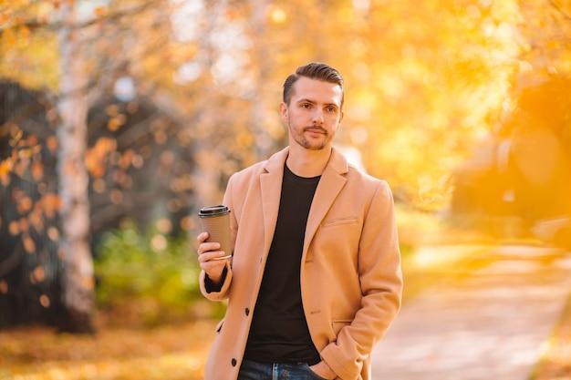 Jeune Homme Buvant Du Café Avec Téléphone En Automne Parc En Plein Air Photo Premium