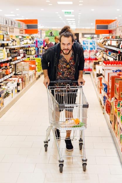 Jeune homme avec caddie au supermarché Photo gratuit