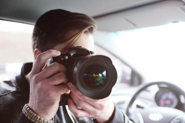 Jeune homme avec une caméra dans la voiture Photo Premium