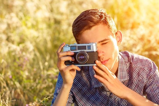Un jeune homme avec une caméra prenant des photos du fond naturel rayons de soleil teinté Photo Premium