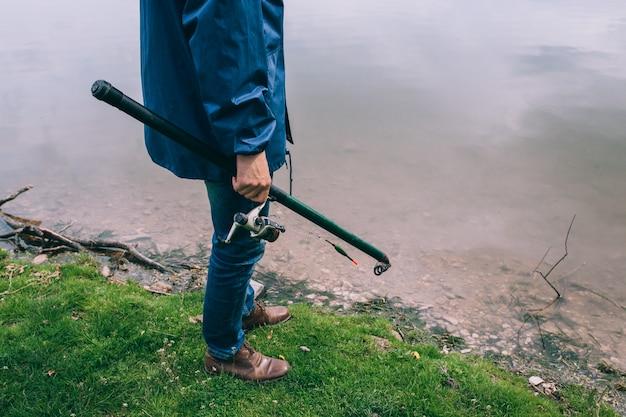 Jeune homme avec une canne à pêche se tenant debout sur le lac Photo Premium