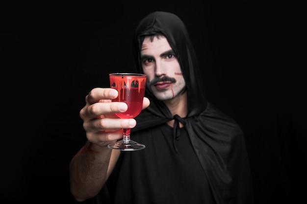 Jeune homme, à, cape, à, capuche, poser, dans, studio, à, verre verre rouge Photo gratuit