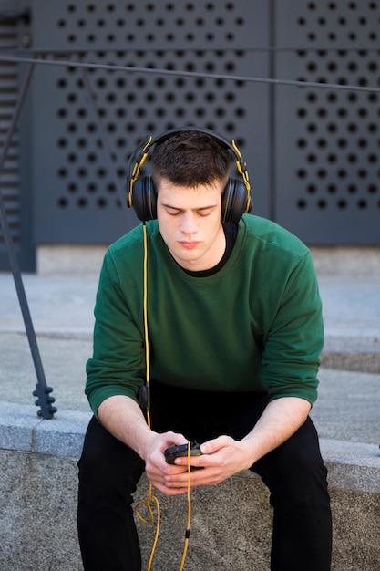 Jeune homme avec un casque d'écoute de la musique Photo gratuit