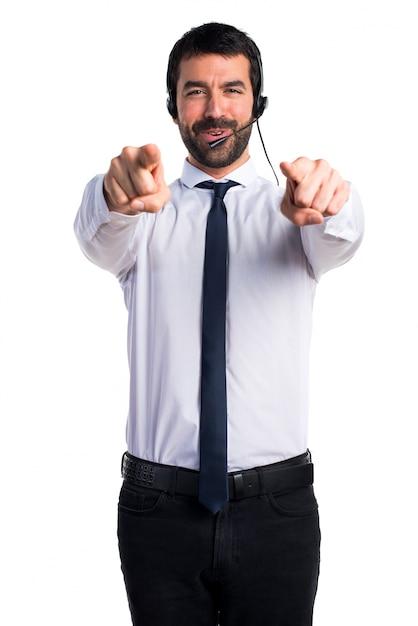 Jeune homme avec un casque pointant vers l'avant Photo gratuit