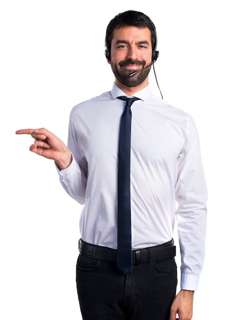 Jeune homme avec un casque pointant vers le côté Photo gratuit