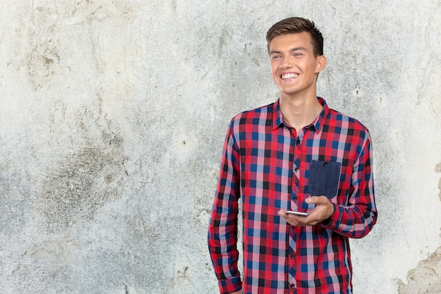Jeune homme casual sms sur son smartphone Photo Premium