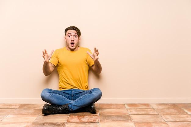 Jeune Homme Caucasien Assis Sur Le Sol Isolé Célébrant Une Victoire Ou Un Succès, Il Est Surpris Et Choqué. Photo Premium