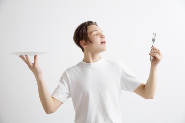 Jeune Homme Caucasien Attrayant Souriant Tenant Un Plat Vide Et Une Fourchette Isolé Sur Fond Gris Photo gratuit
