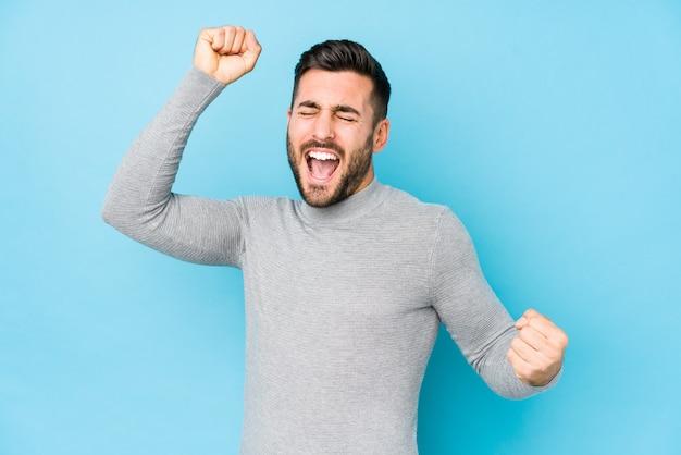 Jeune Homme Caucasien Contre Un Bleu Isolé Célébrant Une Journée Spéciale, Saute Et Lève Les Bras Avec énergie. Photo Premium