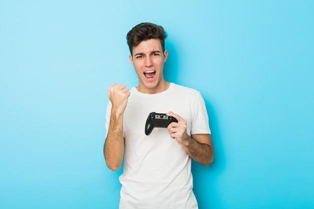 Jeune Homme Caucasien Jouant à Des Jeux Vidéo Avec Contrôleur De Jeu Acclamant Sans Soucis Et Excité. Photo Premium