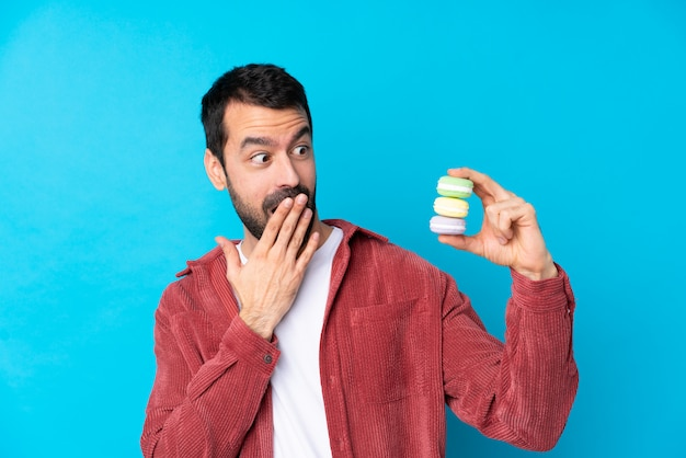 Jeune Homme Caucasien Sur Mur Bleu Isolé Tenant Des Macarons Français Colorés Et Avec Une Expression Surprise Photo Premium