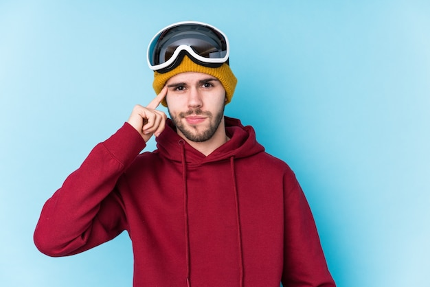 Jeune Homme Caucasien Portant Un Vêtement De Ski Isolé Temple De Pointage Avec Le Doigt, La Pensée, Concentré Sur La Tâche. Photo Premium