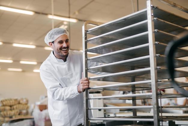 Jeune Homme Caucasien Poussant Des Assiettes Vides Sur Une étagère En Usine Alimentaire. Photo Premium
