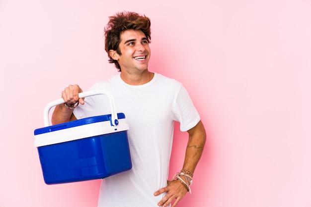 Jeune Homme Caucasien Tenant Un Réfrigérateur Portable Souriant Confiant Avec Les Bras Croisés. Photo Premium