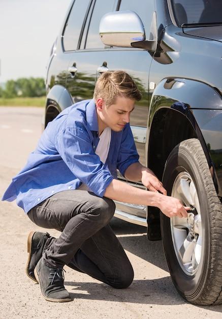 Jeune homme change le pneu crevé de sa voiture. Photo Premium