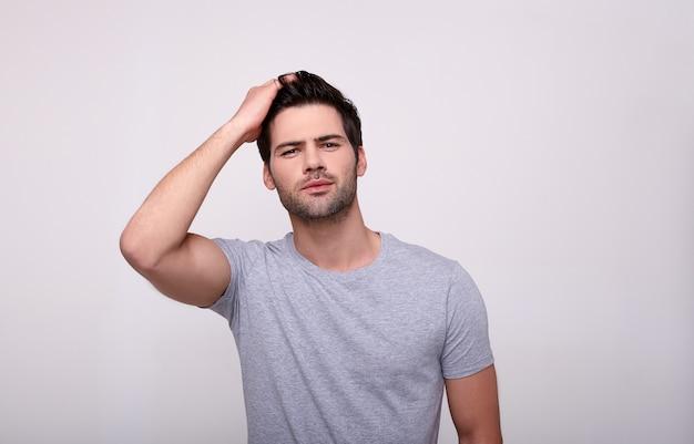 Jeune Homme Charismatique Regardant La Caméra En Se Tenant Debout Contre Le Gris. Photo Premium