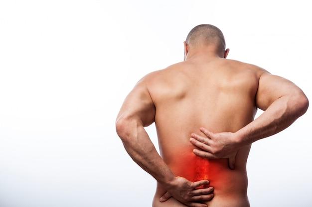 Jeune homme chauve sportif physique retient un dos malade Photo Premium