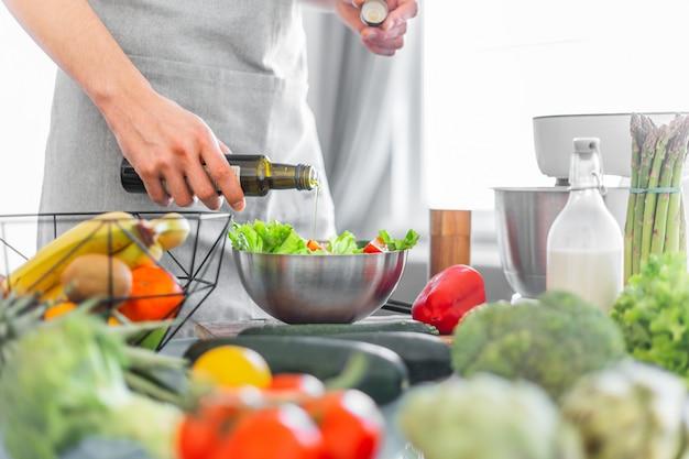 Jeune homme chef cuisine saine salade Photo gratuit