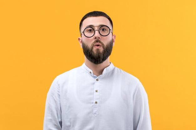 Jeune Homme En Chemise Blanche Avec Barbe Et Lunettes Avec Expression Surprise Photo gratuit