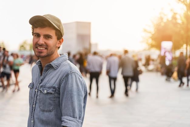 Jeune homme avec une chemise souriante dans une rue Photo gratuit