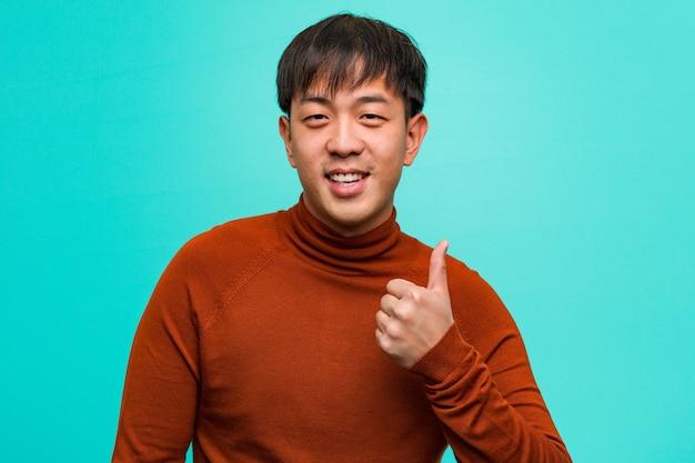 Jeune homme chinois souriant et levant le pouce Photo Premium