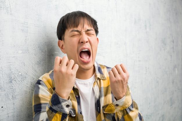 Jeune homme chinois visage closeup très peur et peur Photo Premium