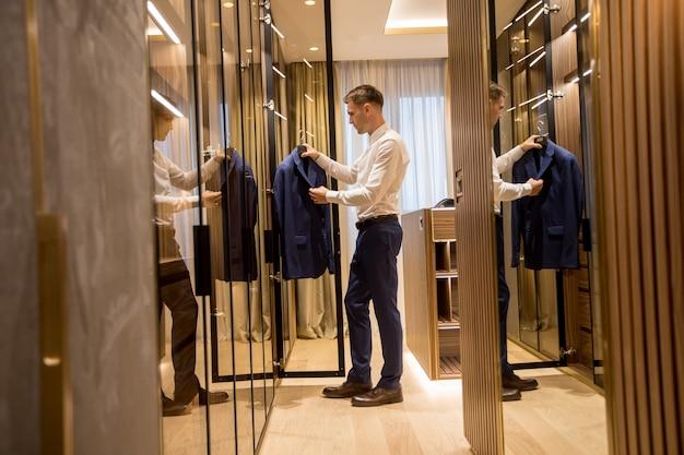 Jeune Homme Choisissant Des Vêtements De Garde-robe Dans Le Hall De L'appartement Contemporain ...