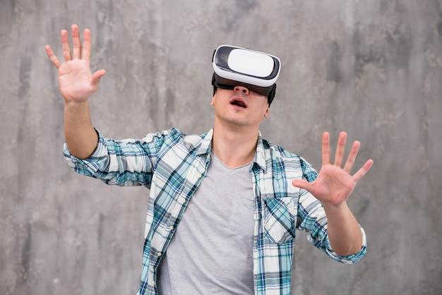 Jeune homme choqué dans un casque de réalité virtuelle Photo gratuit