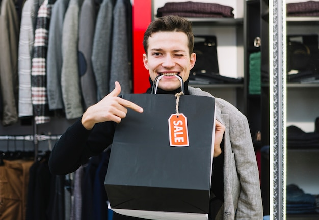 Jeune homme clignant de l'oeil tenant des sacs dans sa bouche Photo gratuit