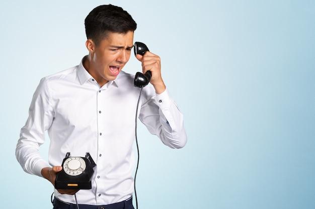 Un jeune homme en colère et irrité crie dans le combiné téléphonique Photo Premium