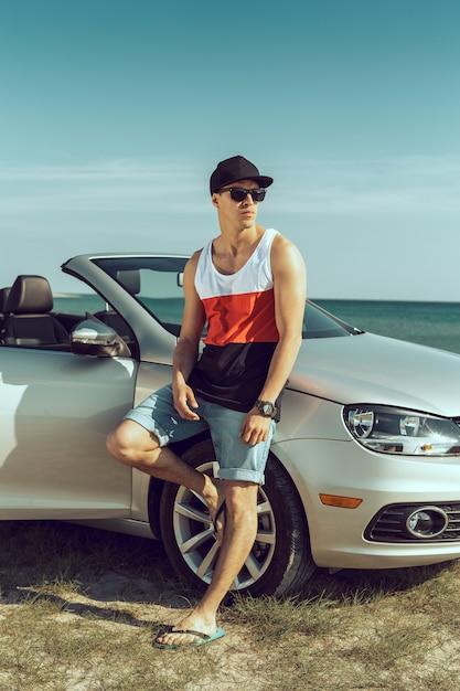 Jeune homme conduire une voiture sur la plage Photo Premium