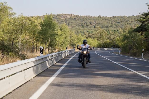 Jeune homme conduisant une moto sur route dans les montagnes par journée ensoleillée. Photo Premium