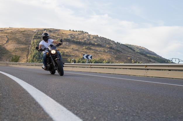 Jeune homme conduisant une moto sur route tournant dans une courbe dans les montagnes par journée ensoleillée. Photo Premium