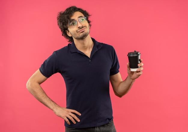 Jeune Homme Confiant En Chemise Noire Avec Des Lunettes Optiques Tient Une Tasse De Café Et Met La Main Sur La Taille Isolée Sur Un Mur Rose Photo gratuit