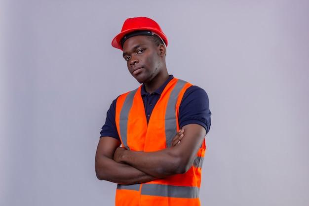 Jeune Homme De Constructeur Afro-américain Portant Un Gilet De Construction Et Un Casque De Sécurité Debout Avec Les Bras Croisés à La Suspecte Photo gratuit